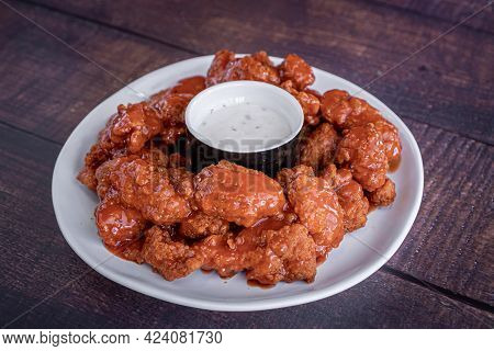 Delicious Chicken Wings Marinated In Buffalo Sauce With A Ranch Dressing Served On A White Plate.
