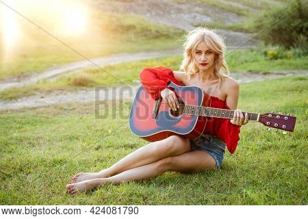 Woman In Red Grass With Red Guitar. Girl Musician Plays The Guitar Outdoors. Blonde Caucasian Appear