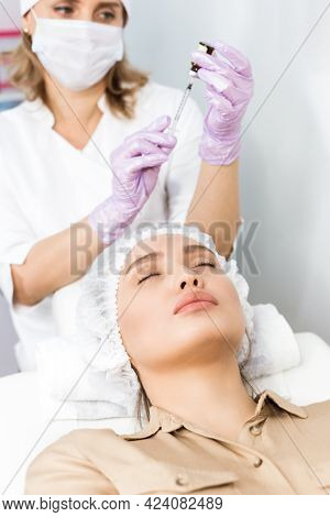 The Beautician Is Picking Up A Syringe For Injection. Woman Undergoing Facelift And Rejuvenation Pro
