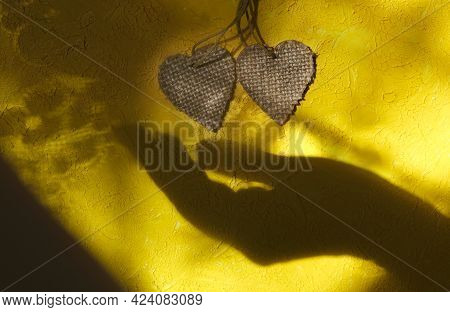 Blurred Shadow Of Female Hand And Two Wooden Heart On Rough Yellow Wall Background. Sunlight And  Cr