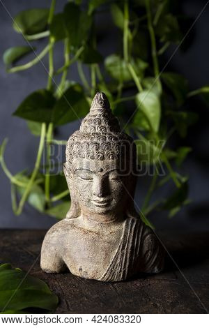 Statuette Of Buddha On A Dark Background Copy Space For Text Vertical Photo