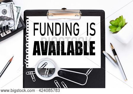 Funding Is Available. Text On A White Sheet Of Paper Near A Magnifying Glass M Flowerpot In A Pot