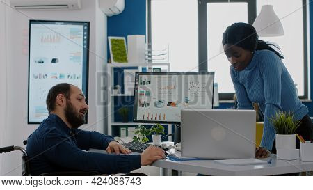 African Entrepreneur Making Project Presentation For Invalid Handicapped Colleague Sitting Immobiliz