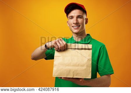 Delivery Person Holding Parcel With Food Delivery Against Yellow Background