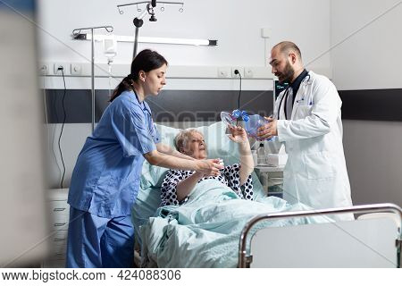 Doctor And Medical Nurse Rushing To Help Senior Woman Breath, In Hospital Room Using Espiratory Mask