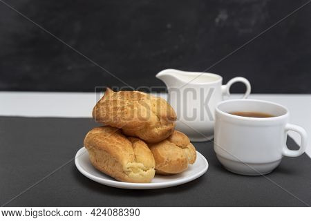 Homemade Delicate Profiteroles And Cup Of Coffee. Traditional French Eclairs. Side View.