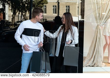 Happy Young Couple With Shopping Bags In Mall. Guy And Girl Over Shop Window Background. Black Frida
