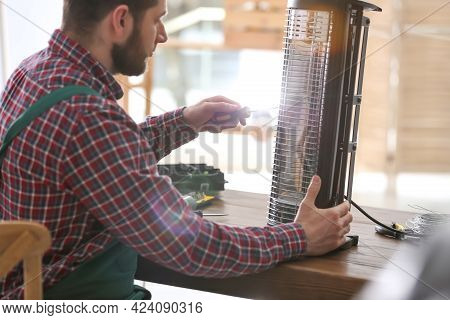 Professional Technician Repairing Electric Halogen Heater With Screwdriver At Table Indoors