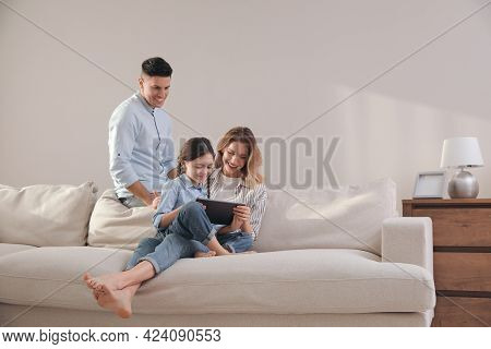 Family With Little Daughter Using Tablet On Sofa In Living Room