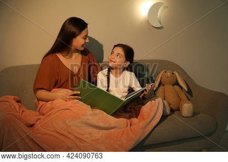 Little Girl With Mother Reading Book In Living Room Lit By Night Lamp