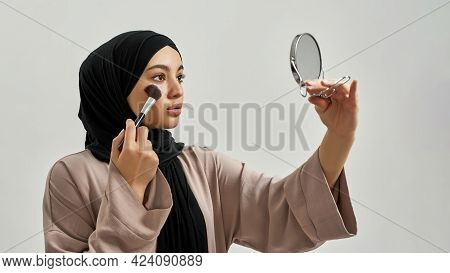 Pretty Young Arabian Girl Wearing Black Hijab And Using Decorative Cosmetics While Looking Into Mirr