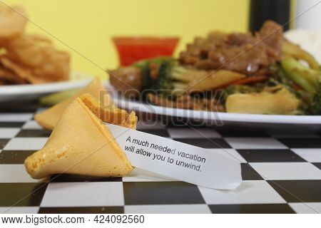 Fortune Cookie On Table With Chinese Food In Background, A Much Needed Vacation Will Allow You To Un