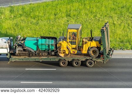 Transporting The Road Roller And Asphalt Paver On The Cargo Platform By The Truck Trailer