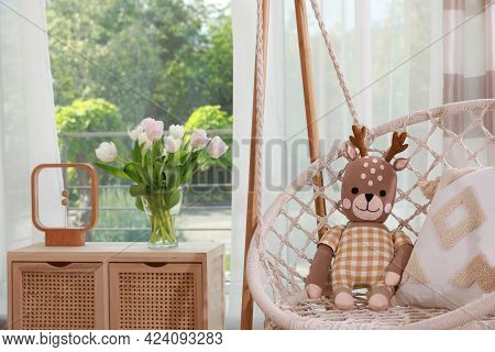 Swing Chair With Toy Reindeer Near Window Indoors. Interior Design