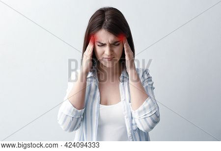 Young Woman Suffering From Migraine On White Background