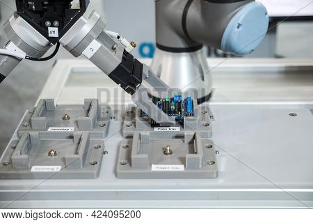 Close-up Industrial Gripping Robot Working With Electronic Circuit Board Put On Pass Tray By Automat