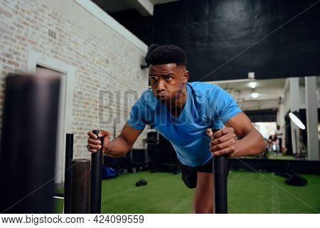 African American Male Working Out Intensely During Cross Fit Training. Male Athlete Pushing The Sled