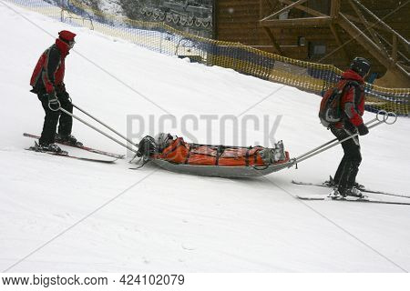 Rescuers Evacuate The Victim From The Slope At A Ski Resort