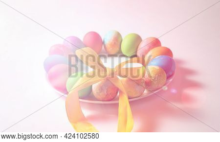 Colored Eggs For Easter On A White Background Are Laid Out In A Circle Surrounded By A Ribbon Bow-kn