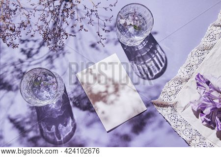 Two Glasses With Water And Card Note With Iris Flower On Pastel Lilac Background With White Cloth An