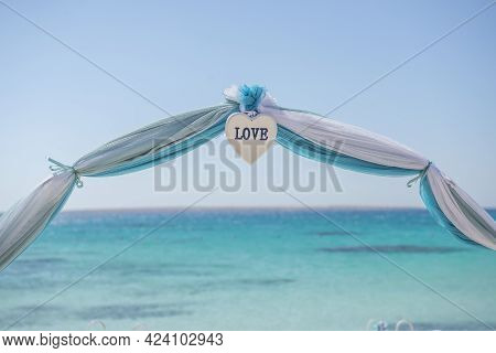 Setup Of Wedding Day Marriage Aisle With Drapes And Arch On Sandy Tropical Beach Paradise To Open Oc