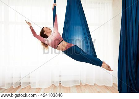 The Girl Is Engaged In Aerial Yoga In A Beautiful Pose In A Hammock Against A Large Window, A Woman