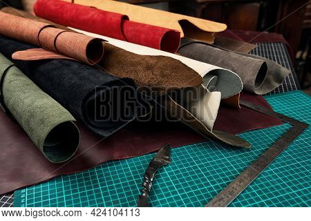 Rolled Up Samples Of Textures Of Genuine Leather Of Different Colors On A Leather Background, On A T