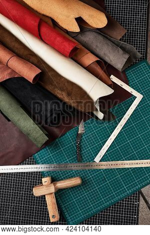 Samples Of Genuine Leather Of Different Colors Are Rolled Up On A Table With Mats And Tools For Cutt
