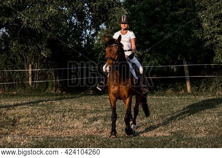 Beautiful Young Athlete In Helmet And White Sports Uniform Trains Riding On Warm Summer Evening . Ac
