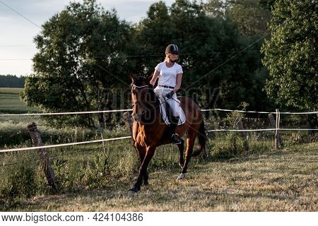 Young Woman In White Sports Clothes Is Practicing Horse Riding .sports And Health. The Right Way Of