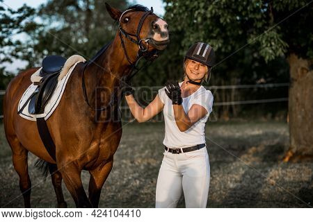 Smiling Young Woman And A Flirty Horse Pose Looking At Camera. Happy Together. Concept Of Happiness