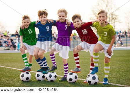 Group Of Happy Junior Soccer Boys In Colorful Jersey Uniforms. Five Joyful Kids With Soccer Football