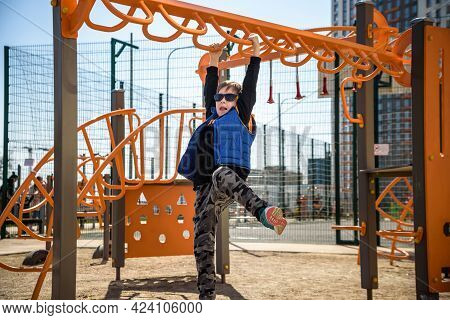 Cute Boy Is Climbing On The Playground In The Schoolyard. He Has A Very Happy Face And Enjoy This Ad