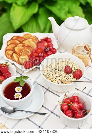 Breakfast Outside. Strawberries, Cherries, Mini Pancakes Oatmeal. And Honey On Table. Summer Picnic.