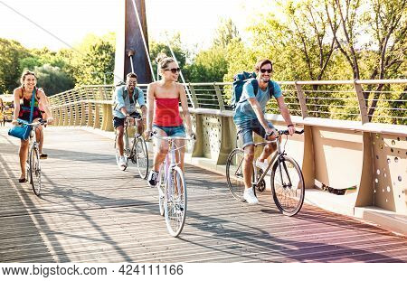 Happy Milenial Friends Having Fun Riding Bike At City Park Bridge - Life Style Concept With Young Hi