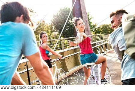 Happy Friends Having Fun Riding Bike At City Park - Friendship Life Style Concept With Young Milleni