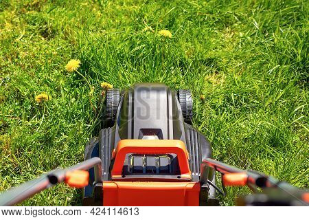 Close-up Of A Black Lawn Mower In The Backyard With Green Grass Grown Up.