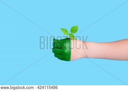 Green Children's Hand Holding A Bent Plant On A Blue Background.concept Of Forest Conservation. Envi