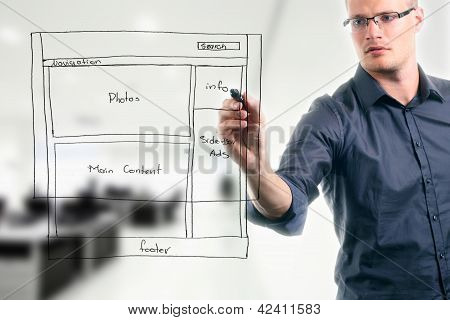 young man drawing website development wireframe in the office poster