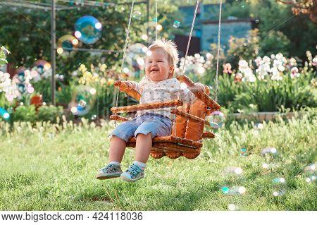 Happy Baby Girl Having Fun On A Swing. Sunny Playground In A Kindergarten. Sunny Playground In The B