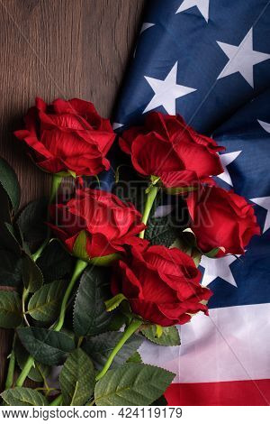 Concept Of Independence Day Or Memorial Day. Flag And Rose Over Dark Wooden Table Background.