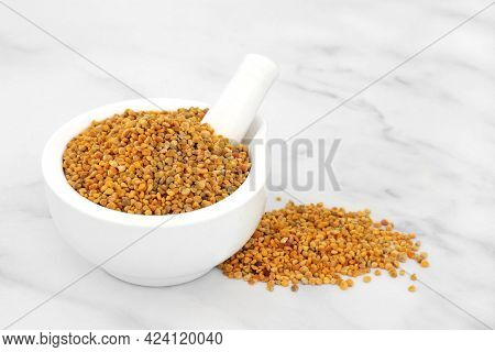 Bee pollen in a mortar with pestle used in natural herbal medicine to relieve inflammation, influenza, boosts liver health, strengthens immune system, reduces stress and used as a dietary supplement.