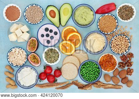 Mood stabilizing foods  herbal medicine to treat bipolar disorder  manic depression with foods high in omega 3, protein, vitamins, selenium, magnesium, serotonin  tryptophan. Flat lay on mottled blue.