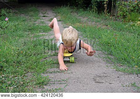Little Boy Lying Down For A Drive On A Skateboard.