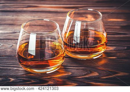 Two Glass Of Whiskey, Cognac, Brandy On A Dark Brown Wooden Table. Bourbon. Strong Alcohol Drink Clo