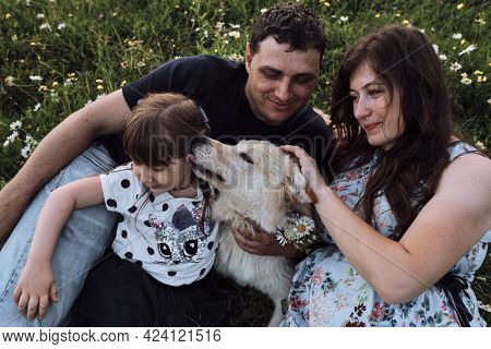 Young Caucasian European Happy Family With Half Breed White Swiss Shepherd Is Enjoying Life. Mom Dad