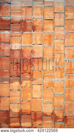 Hand made brick wall made from narrow bricks, abstract background texture. Red grunge brick in the wall with gray putty. Brick screen saver. Empty brick wall.