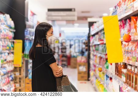 Asian Woman With Protective Mask Choosing Food In Supermarket During Coronavirus Pandemic