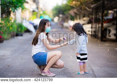Family Prevent Spread Covid-19 Coronavirus Disease Concept. Mother Spit Alcohol Spray On Her Daughte