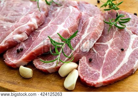 Sliced  Fresh Pork Steaks On Cutting Board With Ingredients For Cooking